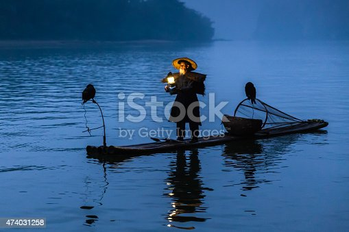 Traditional chinese 75 year old senior fisherman in traditional clothes and chinese hat on his wooden fishing raft with two gray herons fishing on the Li River in the early morning fog light at sunrise illuminated by a petroleum lamp he`s holding in his hands. Tranquil, moody original scene with real chinese fisherman shot at Xing Ping, close to the city of Yangshuo County, Guangxi, Guilin, China.