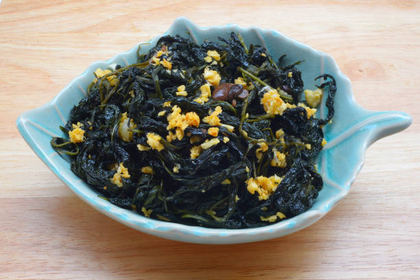 Chinese Traditional Food, Stir Fried Jute Leaves or Mulukhiyah Leaves with Garlics and Fermented Soy Bean. stock photo