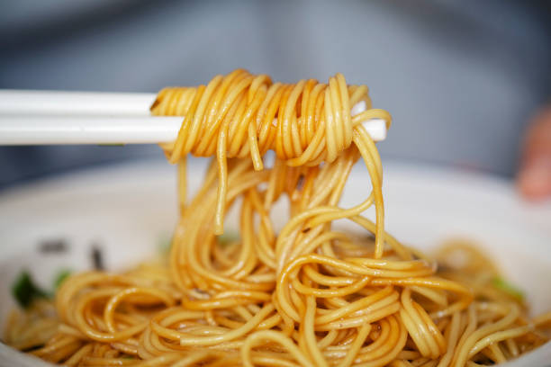 Chinese traditional noodles stirred with olive oil, soy sauce and scallion stock photo
