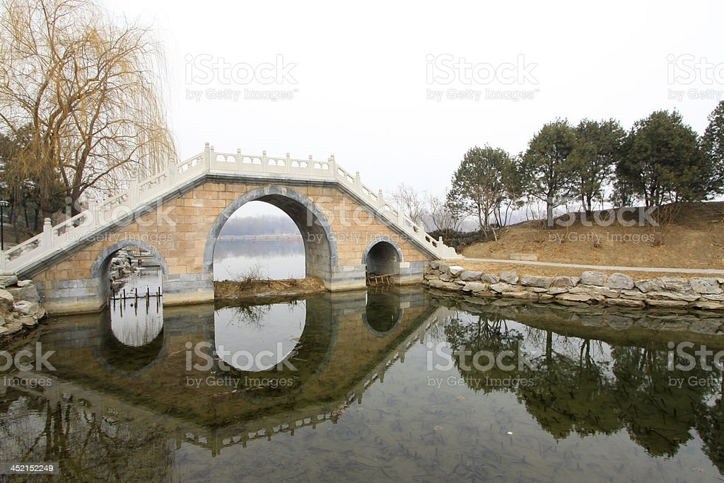 Chinese traditional style stone bridge in the snow stock photo