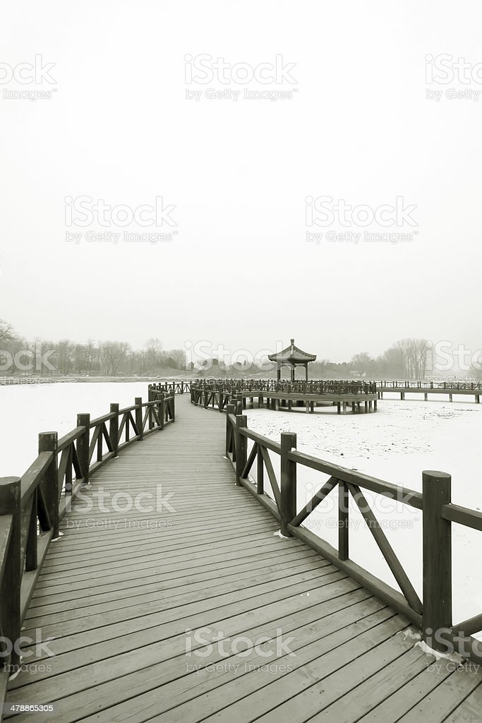 Chinese traditional style wooden bridge in the snow stock photo