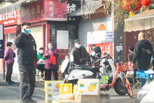 Chinesen tragen chirurgische Maske am Telefon – Foto