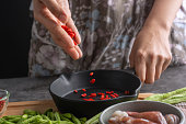 Close Up hands of the housewives scattering Chinese Wolfberry Into the pan to cook And squid and lentils To make healthy food menus.