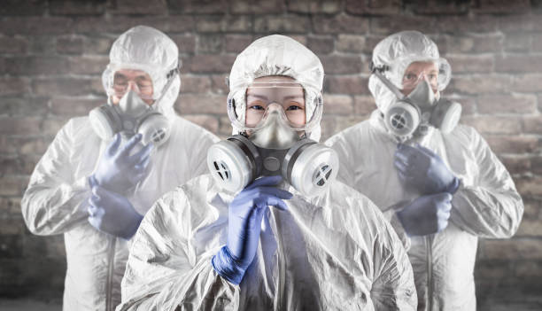 Chinese Woman and Team Behind In Hazmat Suites, Gas Masks and Goggles Against Brick Wall stock photo