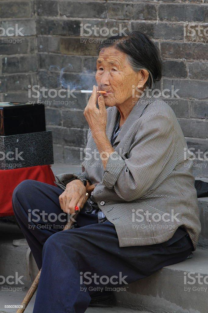 Chinesische Frau bei Rauchen stock photo