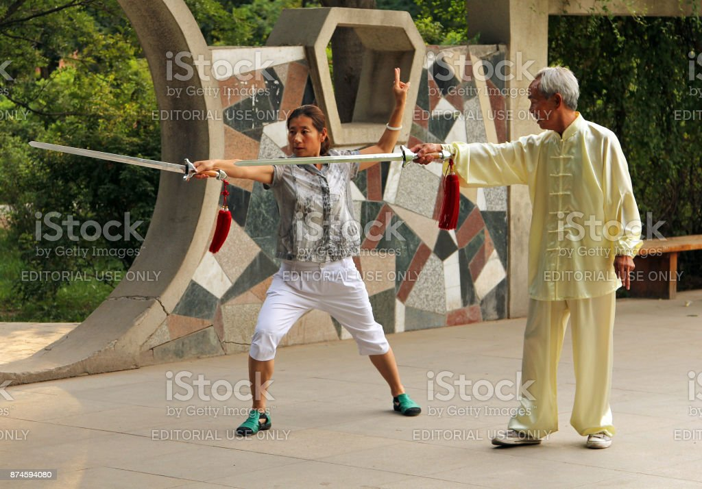 Chinese woman doing Wushu Jian form under the guidance of a mentor stock photo