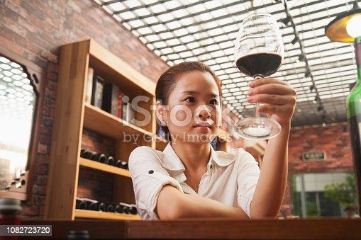 Chinese woman examining glass of wine
