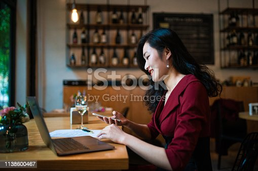 Cheerful Chinese businesswoman filling out some forms, sitting in coffee shop, using lap top