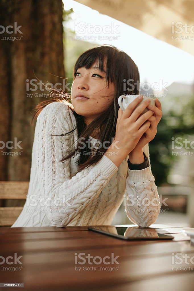 Chinese woman having coffee at outdoor cafe royalty-free stock photo