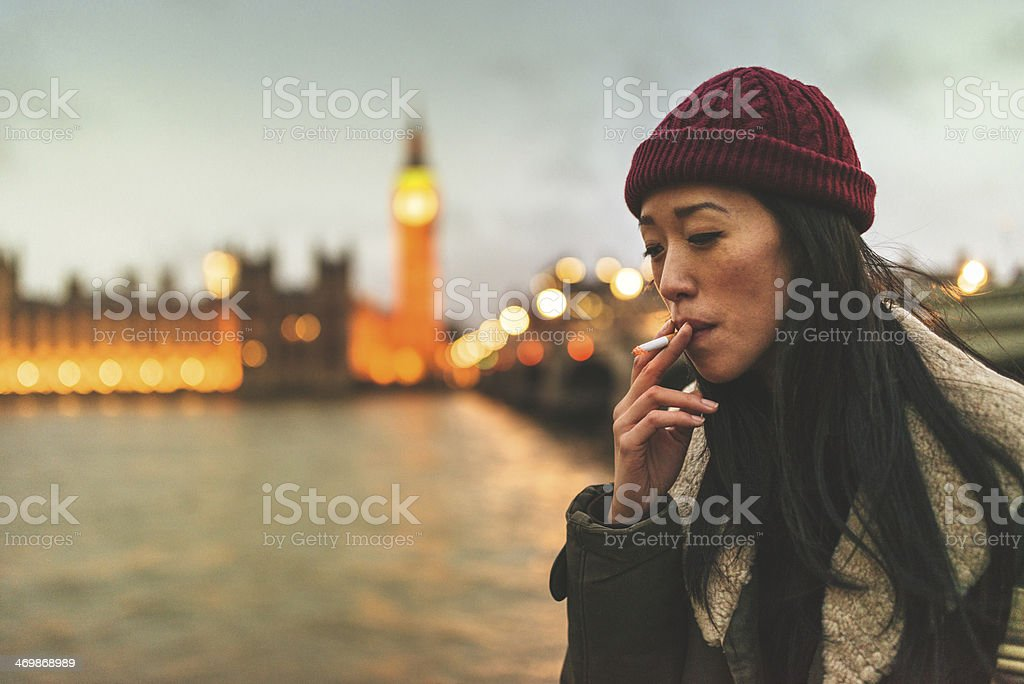 chinese woman in london smoking a cigarette stock photo