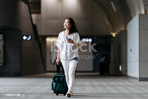 Smiling senior woman arriving in airport and using mobile phone, technology, travel, on the go