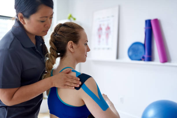 chinese woman massage therapist applying kinesio tape to the shoulders and neck of an attractive blond client in a bright medical office - medicina sportiva foto e immagini stock