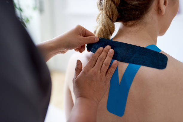 Chinese woman massage therapist applying kinesio tape to the shoulders and neck of an attractive blond client in a bright medical office stock photo