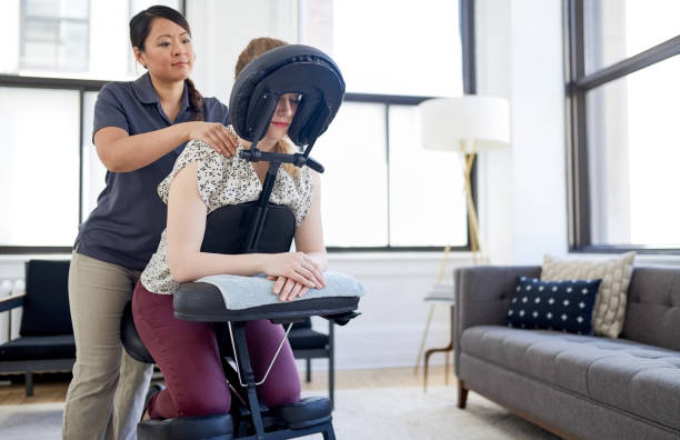 Chinese woman massage therapist giving a neck and back pressure treatment to an attractive blond client at her workplace in a bright office stock photo