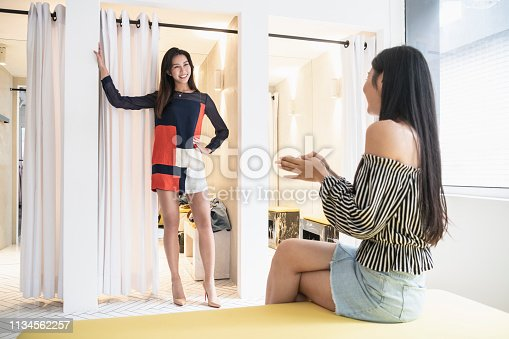 Full length candid portrait of slim woman in her 20s, standing and posing in retro style mini dress, female companion smiling and looking positive, individuality, style and confidence