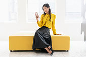 Cheerful mid adult female in smart clothing, resting on mustard colour seat in modern boutique, checking smartphone, retail, shopping, social media