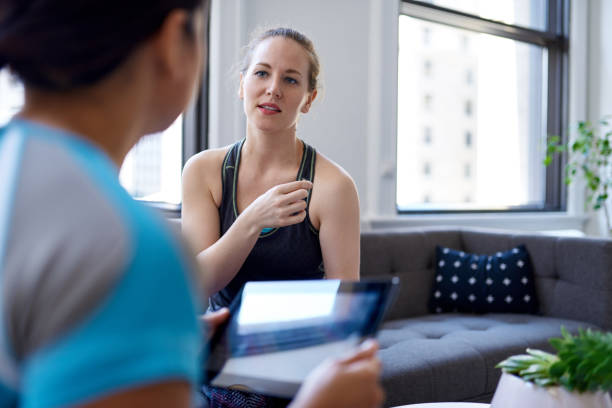Chinese woman physiotherapist talking to a mid-adult caucasian female patient and taking notes on a tablet during a fitness evaluation consultation stock photo