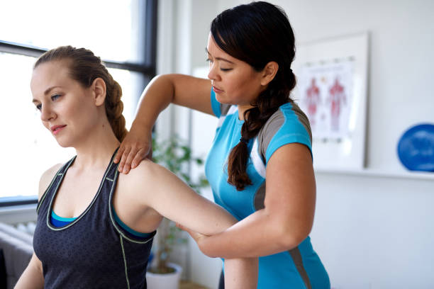 Chinese woman physiotherapy professional giving a treatment to an attractive blond client in a bright medical office stock photo