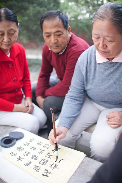 chinesische frau üben kalligraphie im park - gedichte zum ruhestand stock-fotos und bilder