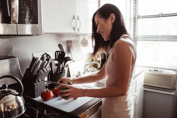 chinese woman preparing food at home stock photo