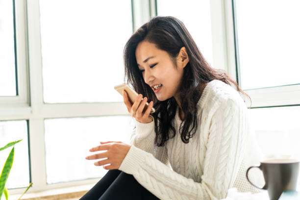 Chinese woman sending voice message at home Young attractive Chinese woman sitting at home , drinking coffee and using smart phone , sending voice message speech recognition stock pictures, royalty-free photos & images