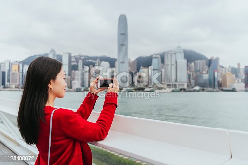 Side view of mid adult female using smartphone to photograph city skyline