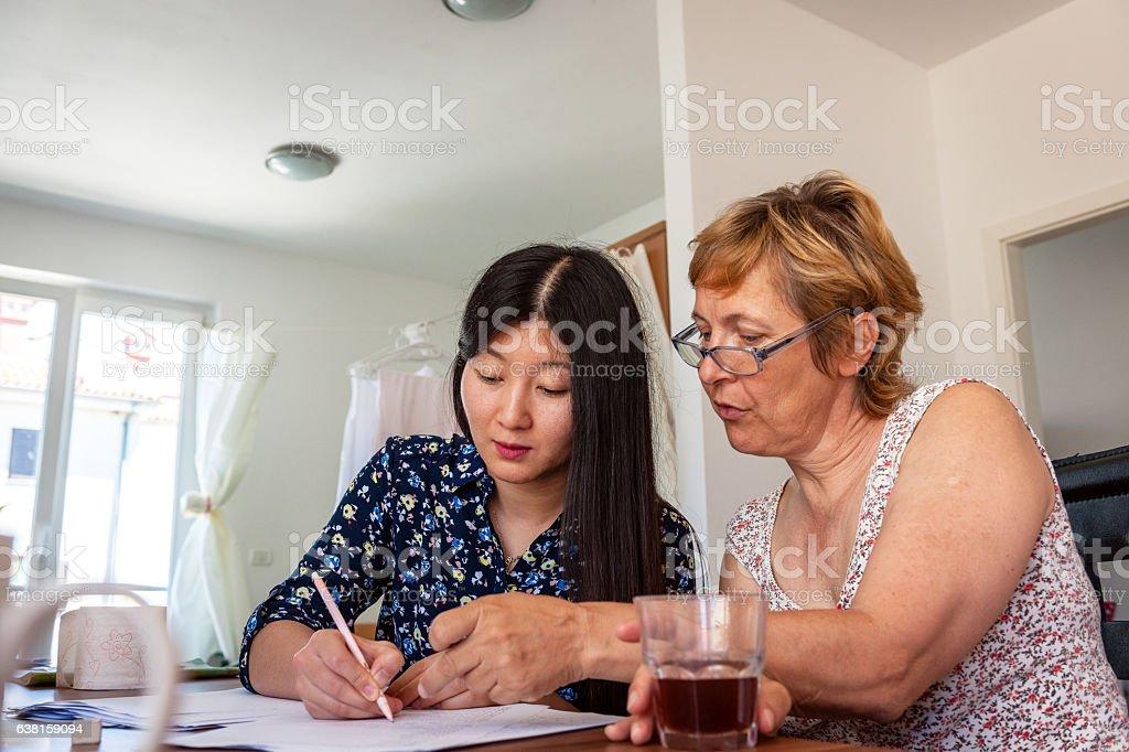 Chinese Woman Teaching Mature Female Caucasian Chinese Numbers, Slovenia, Europe stock photo