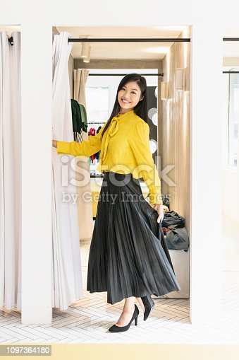 Slim attractive woman  wearing full length black skirt and yellow blouse in fitting room of boutique, twirling, looking at camera, smiling, cheerful, confident