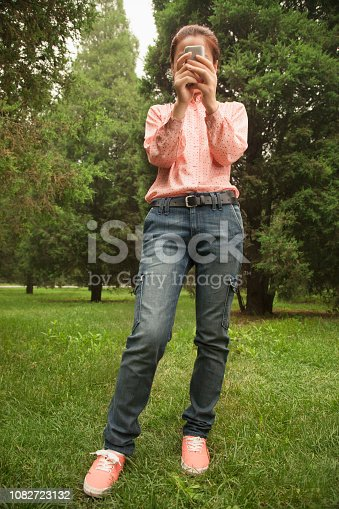 istock Chinese woman using cell phone in a park 1082723132