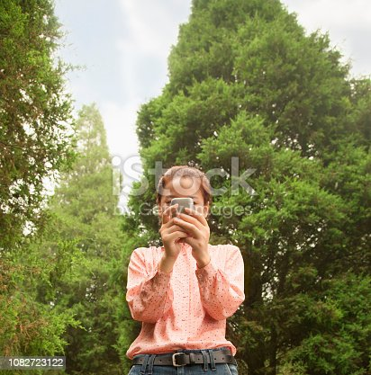 istock Chinese woman using cell phone 1082723122