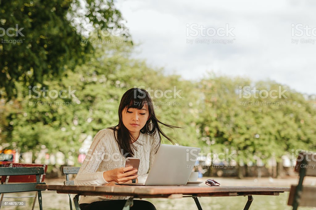 Chinese woman using smart phone in a outdoor cafe stock photo
