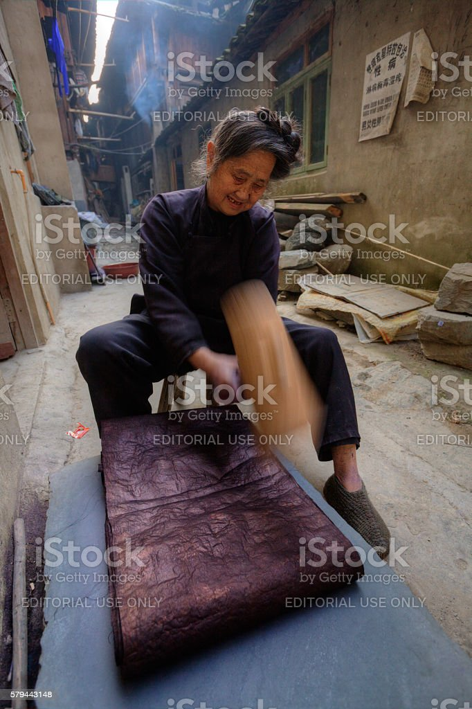 Chinese woman vigorously pounding cloth to make it shine, China. stock photo
