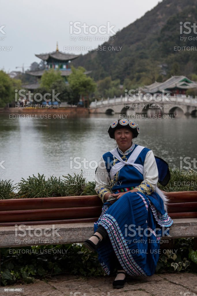 Chinese woman wearing a traditional Bai minority attire sitting in front of the Black Dragon Pool in Lijiang stock photo