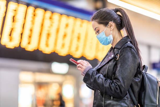 Chinese woman wearing face mask at train station Chinese woman wearing face mask at train station to protect from smog and virus - young asian woman looking at her smartphone with departure arrivals board behind - health and travel concepts airport stock pictures, royalty-free photos & images