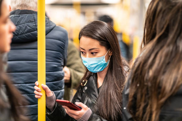 Chinese woman wearing face mask in the train Chinese woman wearing face mask in the train to protect from  virus - young asian woman looking worried and holding a smartphone with many people all around - health and travel concepts east asian ethnicity stock pictures, royalty-free photos & images