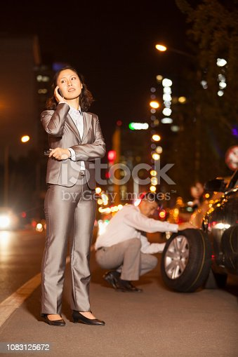 istock Chinese woman with colleague changing car tire 1083125672