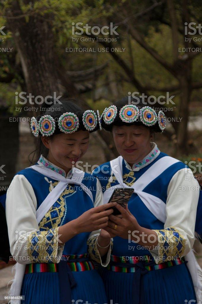 Chinese women wearing a traditional Bai minority attire using a smartphone in Lijiang, Yunnan stock photo