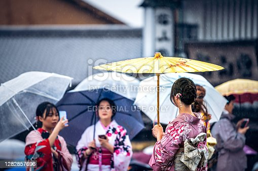 Kyoto, Japan - April 10, 2019: People young women tourists with umbrellas and kimono costumes during rainy day on street near Kiyomizu-dera temple