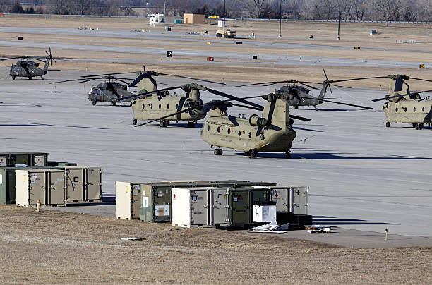 Chinook and Black Hawk Helicopters Fort Riley, KS, USA - February 8, 2015: Chinook and Black Hawk helicopters parked on the tarmac at Fort Riley, Kansas. Fort Riley is a United States Army Installation and home of the 1st Infantry Division. military base stock pictures, royalty-free photos & images