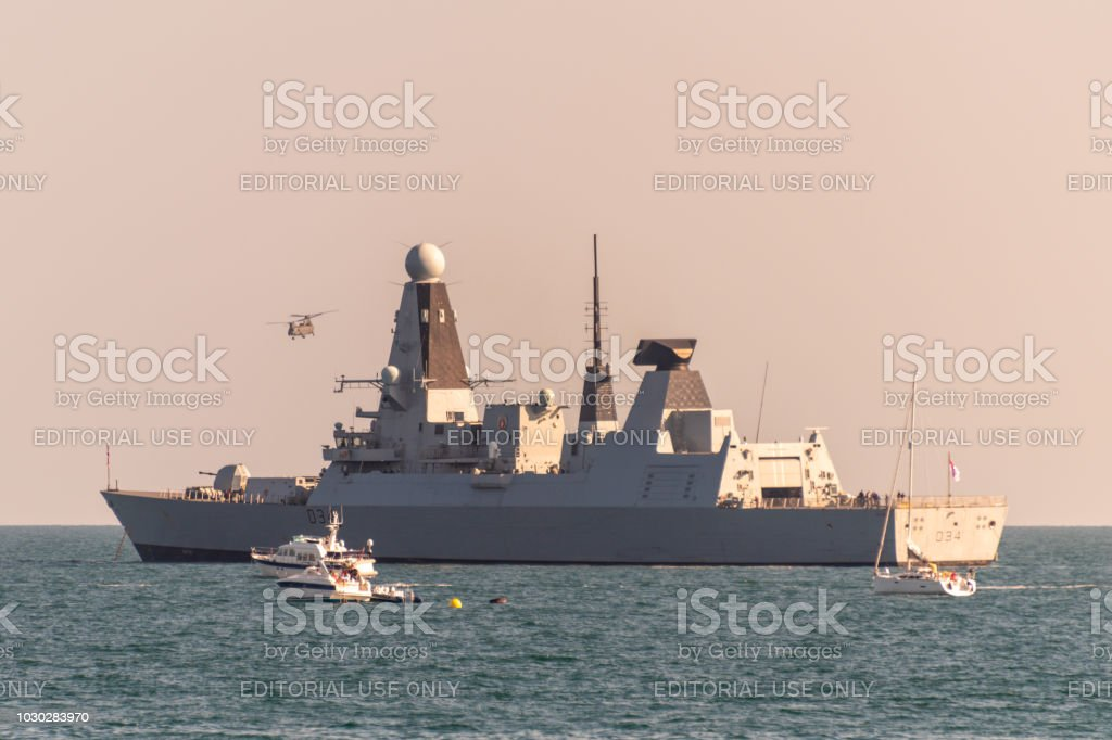 A Chinook helicopter flies over HMS Diamond battleship stock photo