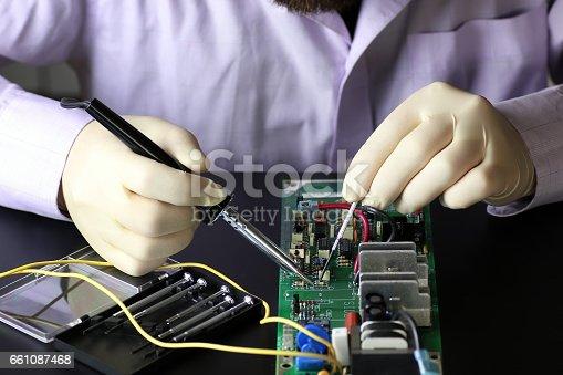 istock chip soldering man hands 661087468