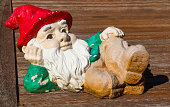 Chipped and cracked but cute decorative garden dwarf with white beard and red cap lounging on wooden deck