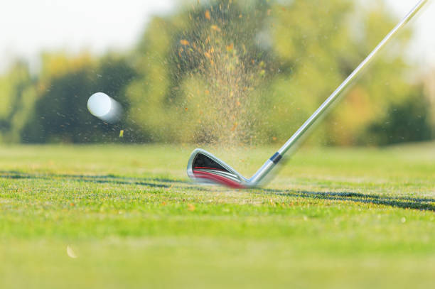 Chipping a golf ball onto the green with golf club stock photo