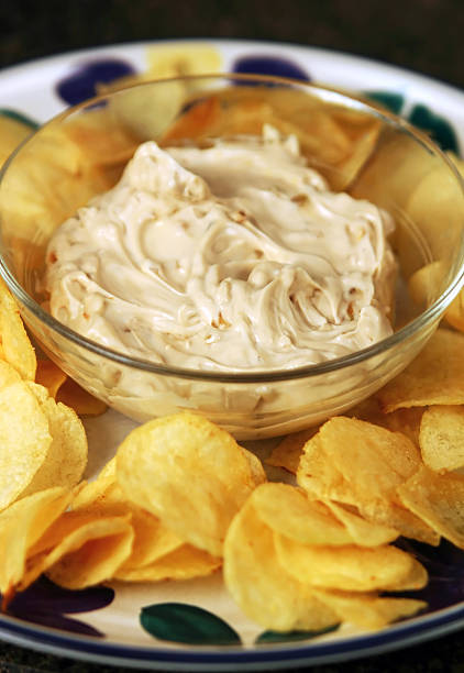 Chips and dip potato chips and onion dip with shallow depth of field (focus on front of dip) shot in studio dipping sauce stock pictures, royalty-free photos & images