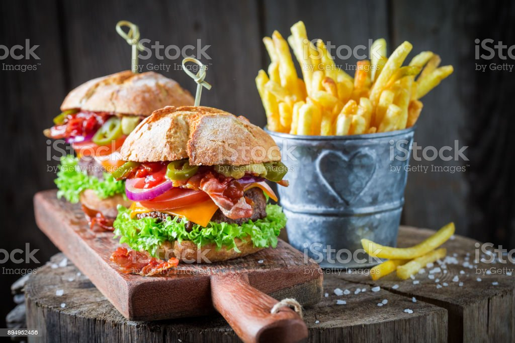 Chips and hamburger with bacon, tomato and beef stock photo