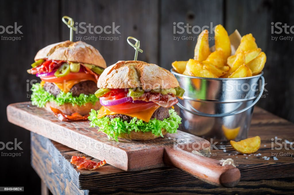 Chips and homemade hamburger made of bacon, tomato and beef stock photo
