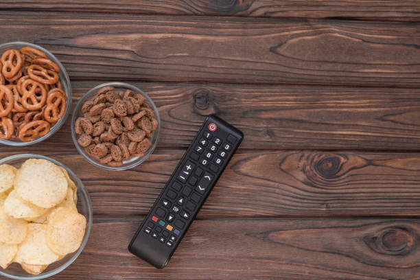 Chips, croutons, snacks. TV remote on the background of a wooden table. leisure. Leisure. stock photo