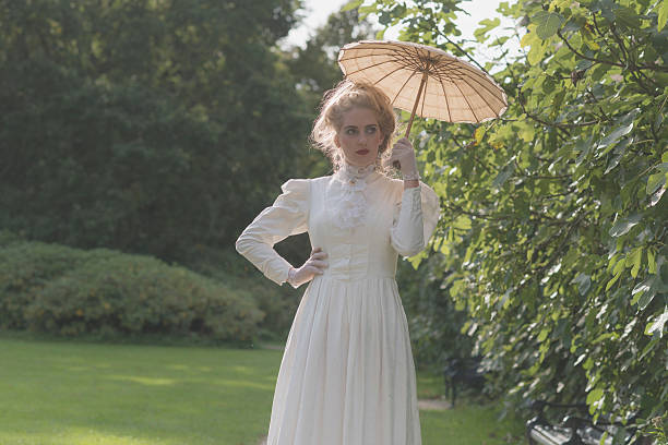 84673016ef74f Chique victorian woman with parasol walking in garden. stock photo