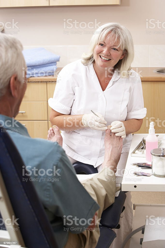 Chiropodist treating client in clinic stock photo