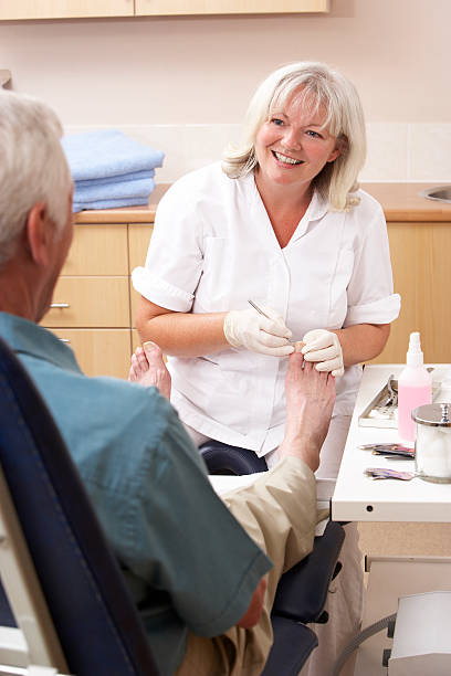 chiropodist treating client in clinic - podiatry stock pictures, royalty-free photos & images